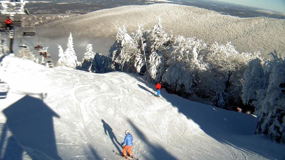 Le mont Sutton enneigé, en janvier 2019. On y voit des skieurs pratiquer leur sport sous un soleil ardent.
