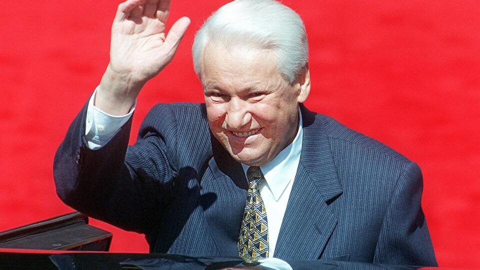 Boris Eltsine, souriant et vêtu d'un complet très classique, salue la foule de la main en sortant d'une voiture noire.
