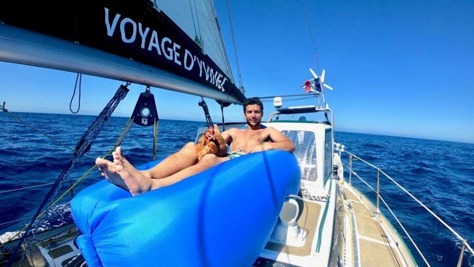 Le navigateur, torse nu, est confortablement installé sur une structure gonflable sur son bateau, caressant sa poule Monique