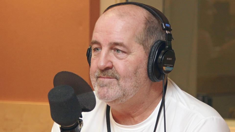 Luc Dionne, un casque d'écoute sur la tête, devant un micro de radio.