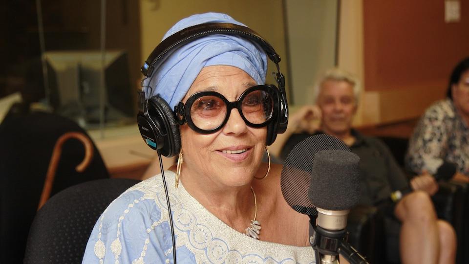 Vêtue de bleu, Francine Grimaldi sourit au micro du studio 18