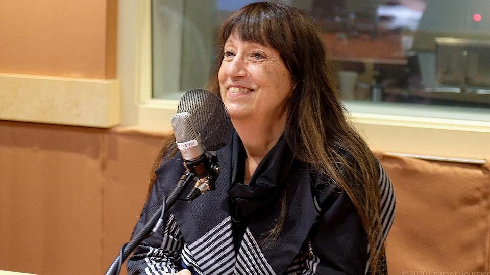 Janine Carreau sourit devant un micro.