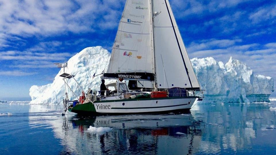 Un bateau à voile approche un iceberg.