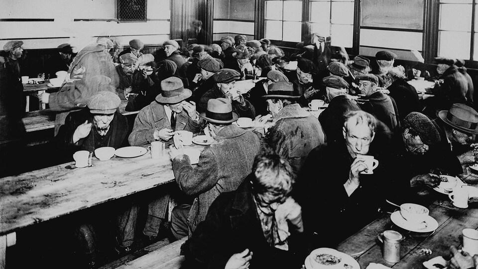 Des personnes mangent dans une soupe populaire des années 1930.