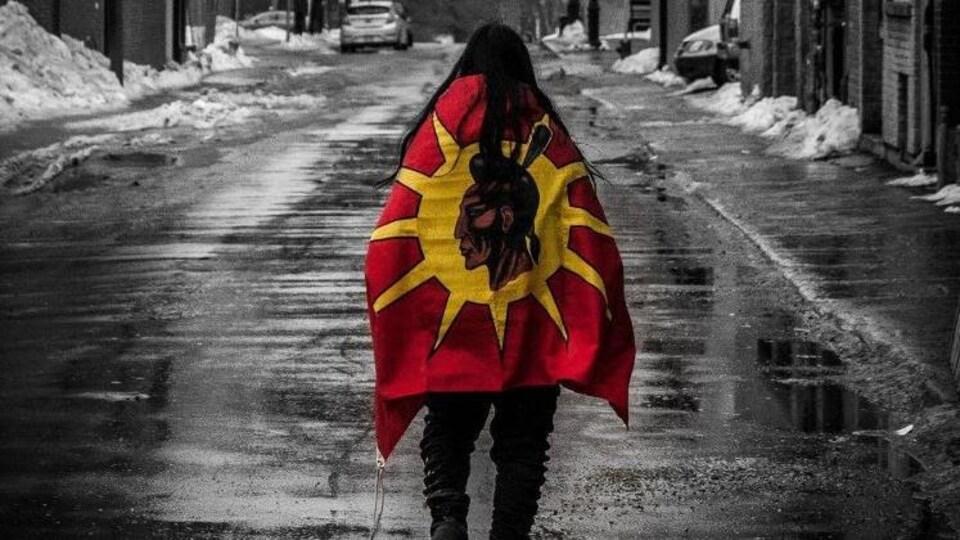 Une personne un drapeau autochtone, marche de dos dans la rue.