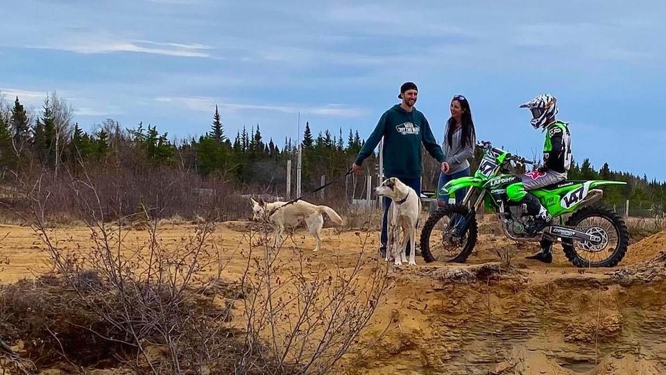 Samuel Power sur une motocross avec un couple d'amis et ses chiens