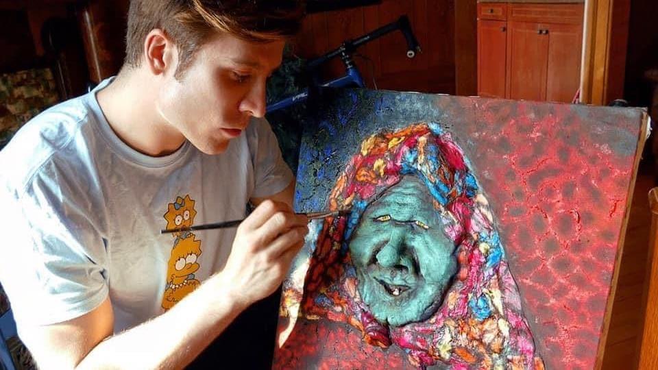 Samuel Rancourt a un pinceau à peintre à la main et fait de la peinture à l'huile.