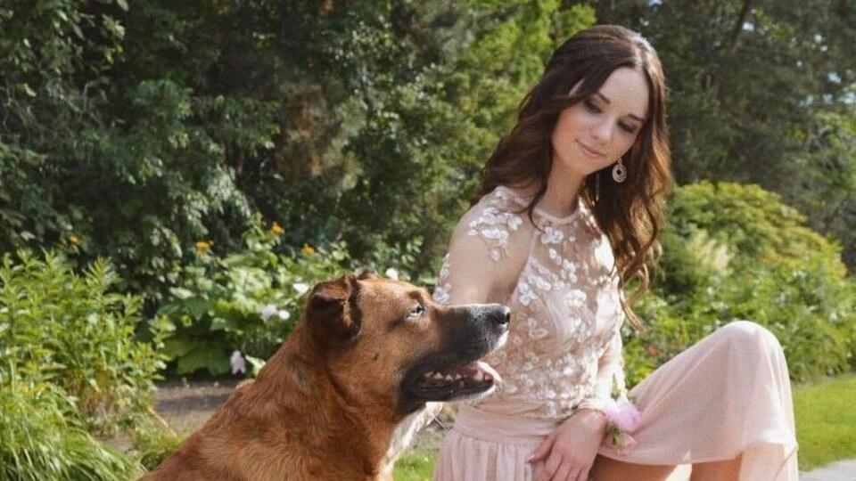 Une jeune femme en robe de bal qui est avec son chien.
