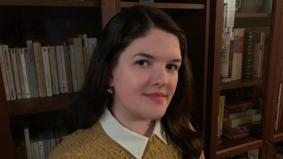Une jeune femme assise devant une bibliothèque.