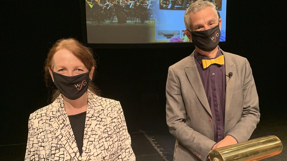 Une femme et un homme portant des masques sont debout devant un podium