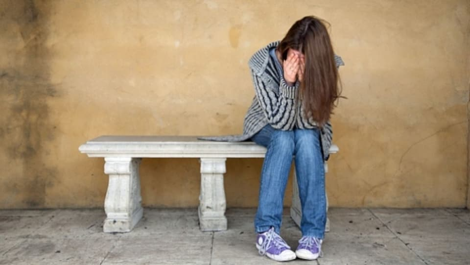 Une jeune fille se tient le visage entre les mains, elle est assise sur un banc.