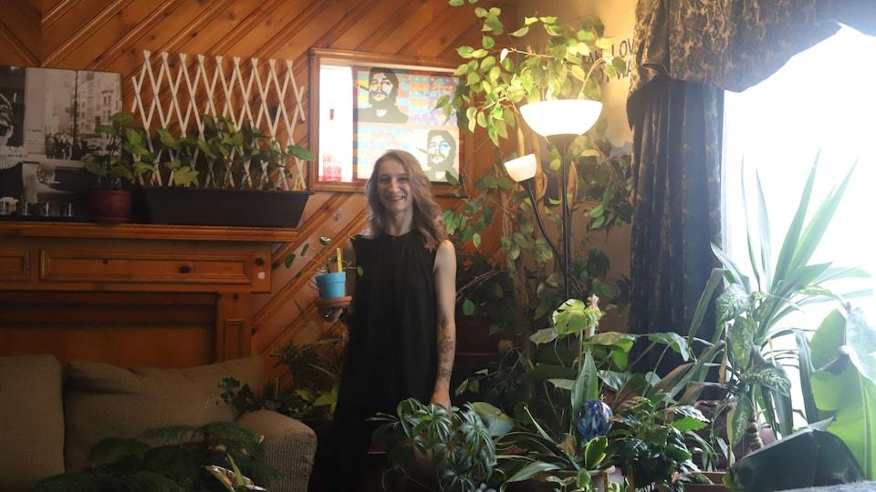 La dame des plantes, entourée de végétaux dans son salon.