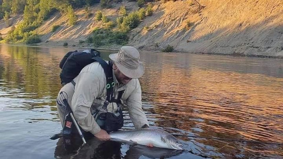 Jocelyn LeBlanc remet un saumon à l'eau.