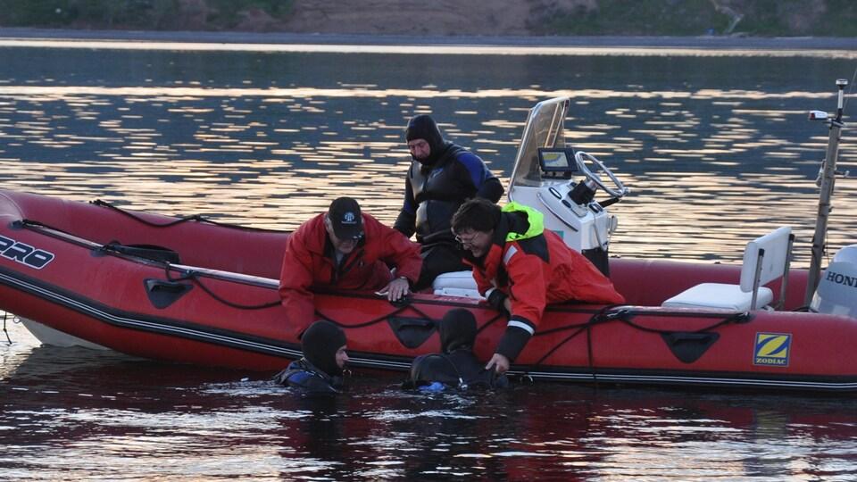 Des bénévoles de la Garde côtière auxiliaire, à bord d'un pneumatique, portent secours à des plongeurs à l'eau.