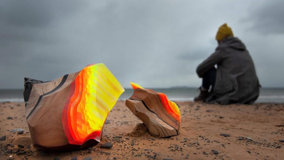 Une sculpture avec l'artiste en arrière plan, sur la plage