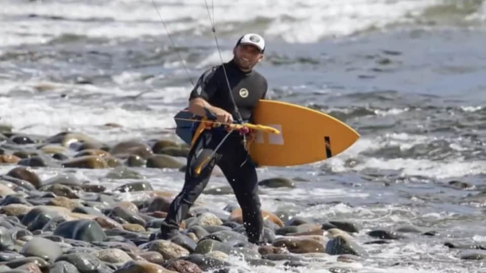 Sébastien Allain, sur le bord de l'eau, qui tient sa planche de kitesurf sous son bras et le cerf-volant.