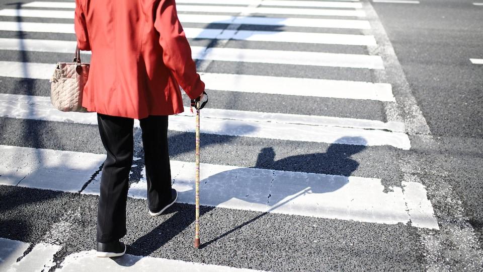 Une femme d'un certain âge traverse la rue à l'aide d'une canne.