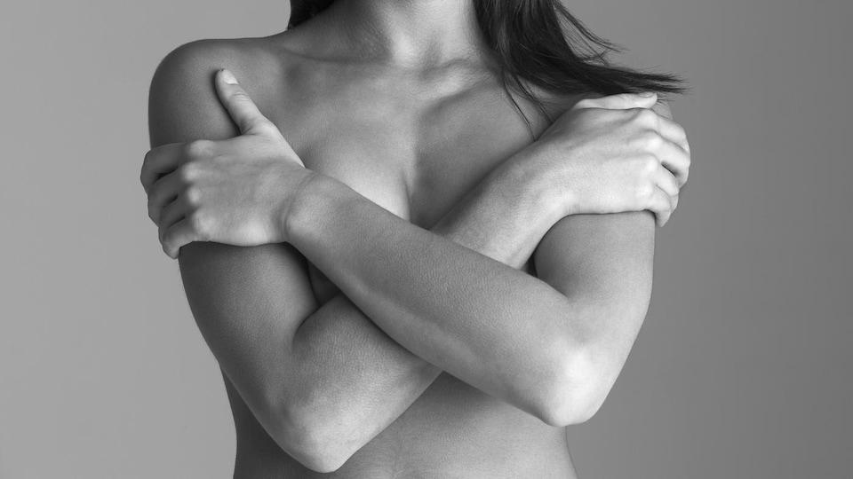 Une femme cache sa poitrine avec ses bras.