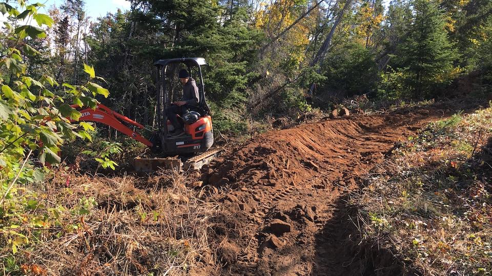 Une petite excavatrice est nécessaire pour aménager les sentiers, après la coupe des arbres
