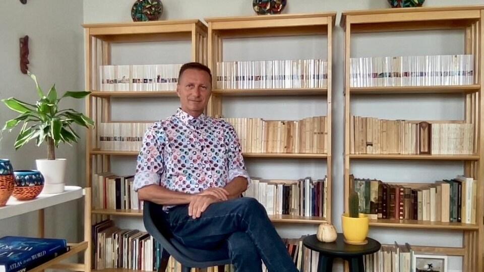 Serge Patrice Thibodeau devant des livres.