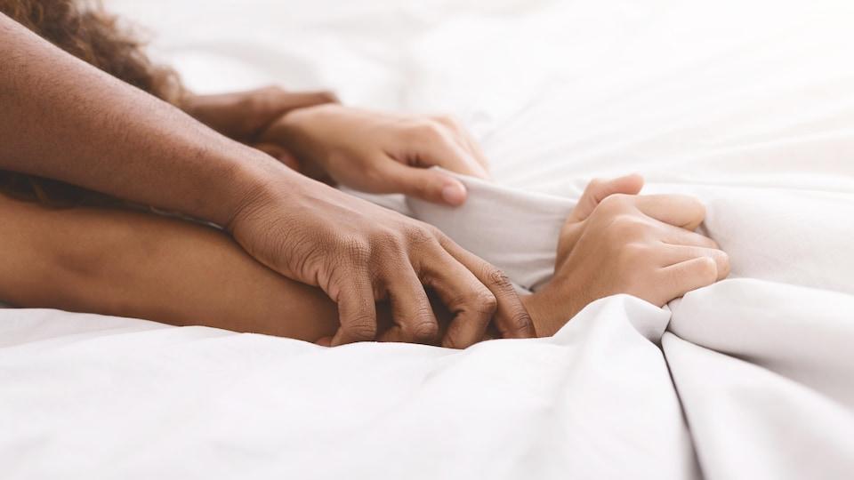 Les bras d'un couple d'entrecroisent sur les draps d'un lit.