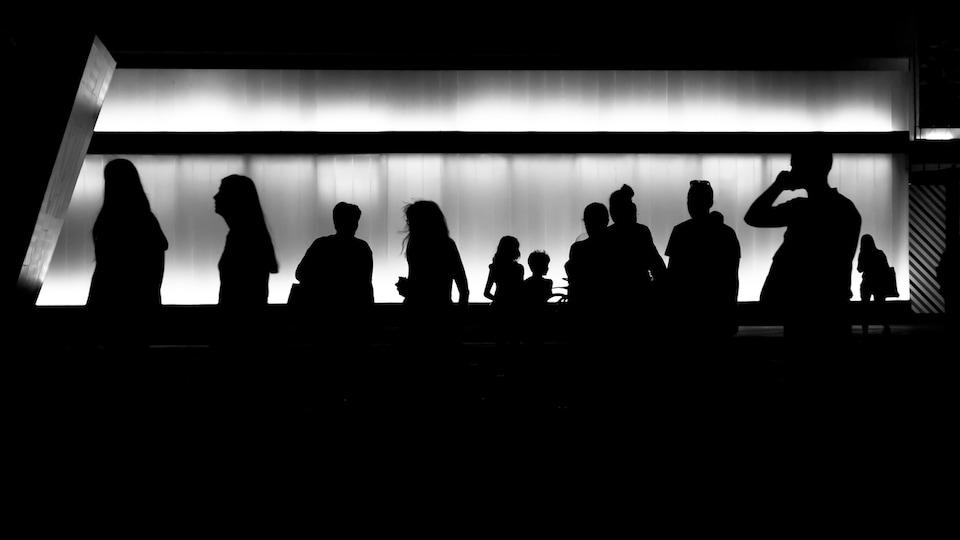 Une douzaine de silhouettes humaines sur un fond métallique illuminé