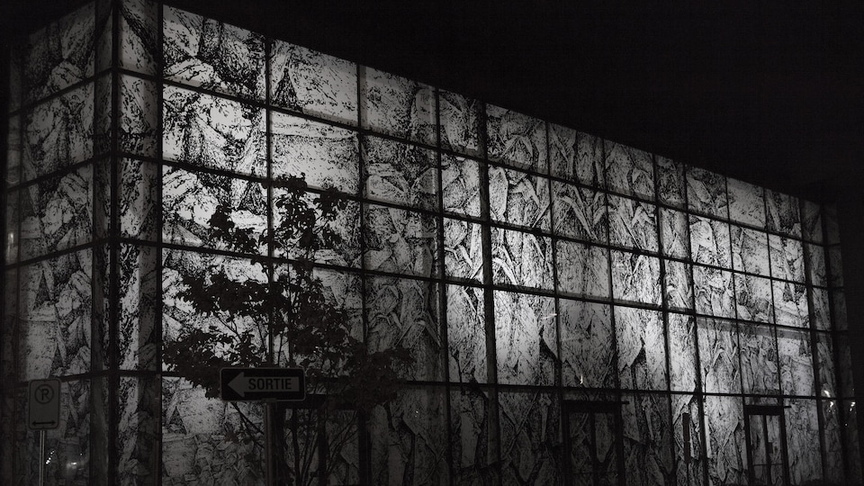 Plusieurs fenêtres d'un bâtiment sont couvertes d'une oeuvre d'art. L'oeuvre est une impression sur papier translucide. Le bâtiment est une bibliothèque.