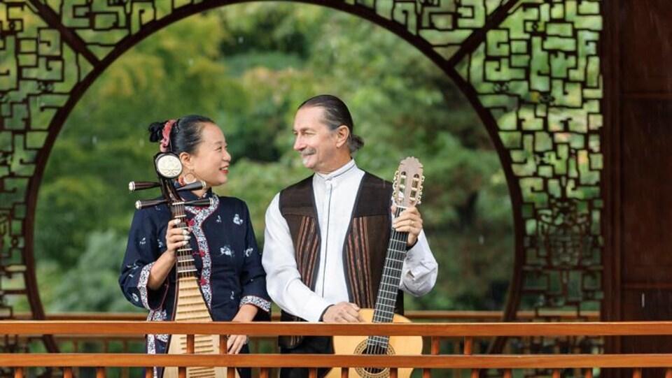 Une musicienne chinoise et un musicien blanc avec leurs instruments dans un jardin chinois