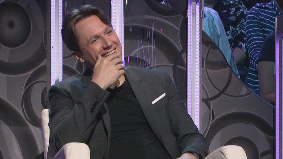 Simon-Olivier Fecteau lors d'une entrevue à la télé. Il sourit et il est assis.