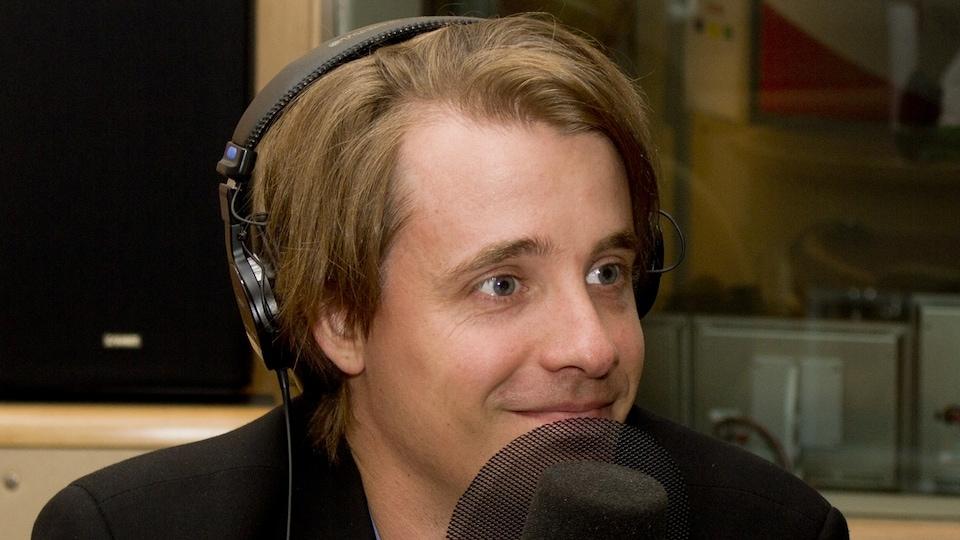 L'économiste Simon Tremblay-Pepin derrière un micro lors d'un passage dans les studios de Radio-Canada.