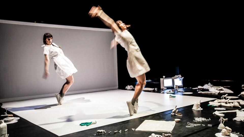 Deux interprètes en danse vêtues de blanc, sur une scène où se trouve plusieurs accessoires de couleur blanche.