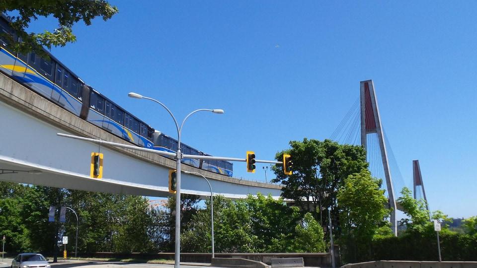 Une rame de quatre voitures de type Mark II du SkyTrain, le métro aérien du Grand Vancouver, approche du pont SkyBridge, qui relie New Westminster à Surrey sur la ligne Expo.