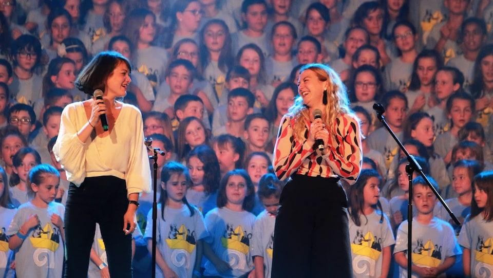 Les Sœurs Boulay, micros à la main, devant une foule de jeunes.