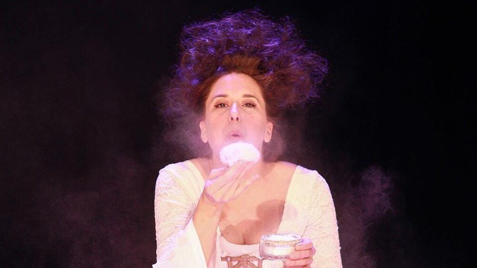 Une photo d'une comédienne vêtue en robe blanche, soufflant sur une poudre de maquillage.