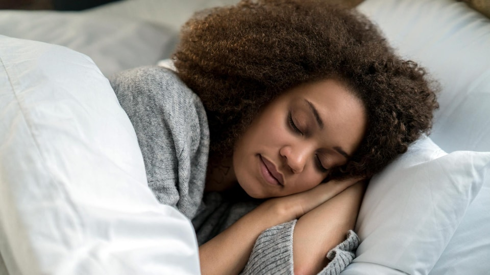 Une femme noire dort dans un lit de draps blancs.