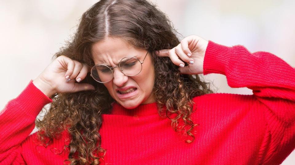 Une jeune fille avec des lunettes met un doigt dans chaque oreille avec un air de dégoût.