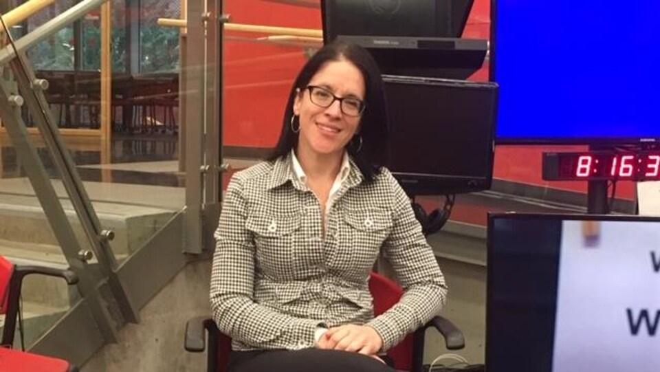 Sonia LeBel est devant des écrans et une horloge et sourit.
