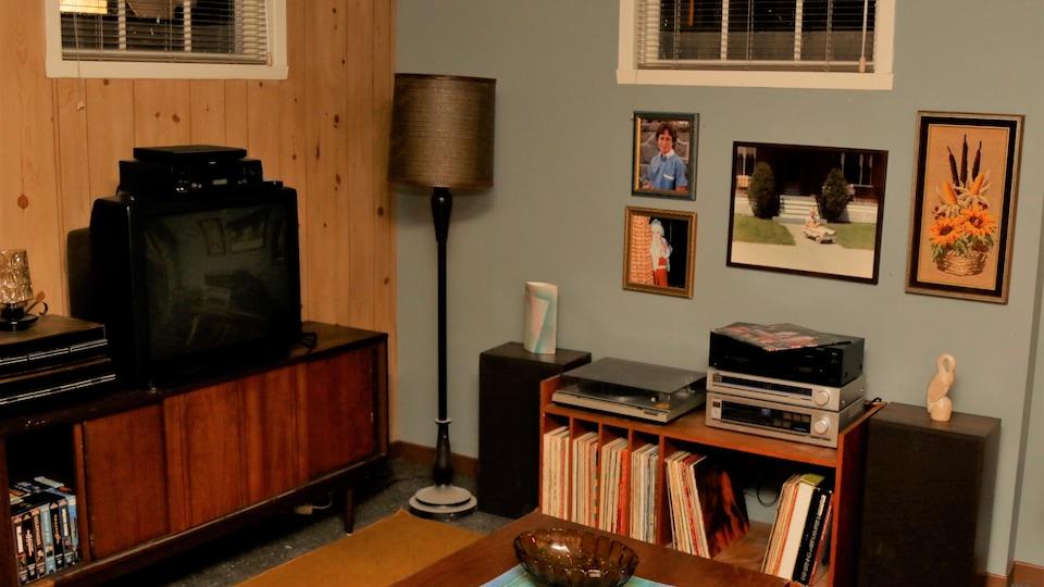 Un sous-sol typique avec des photos sur le mur, un système de son avec une table tournante et une télévision.