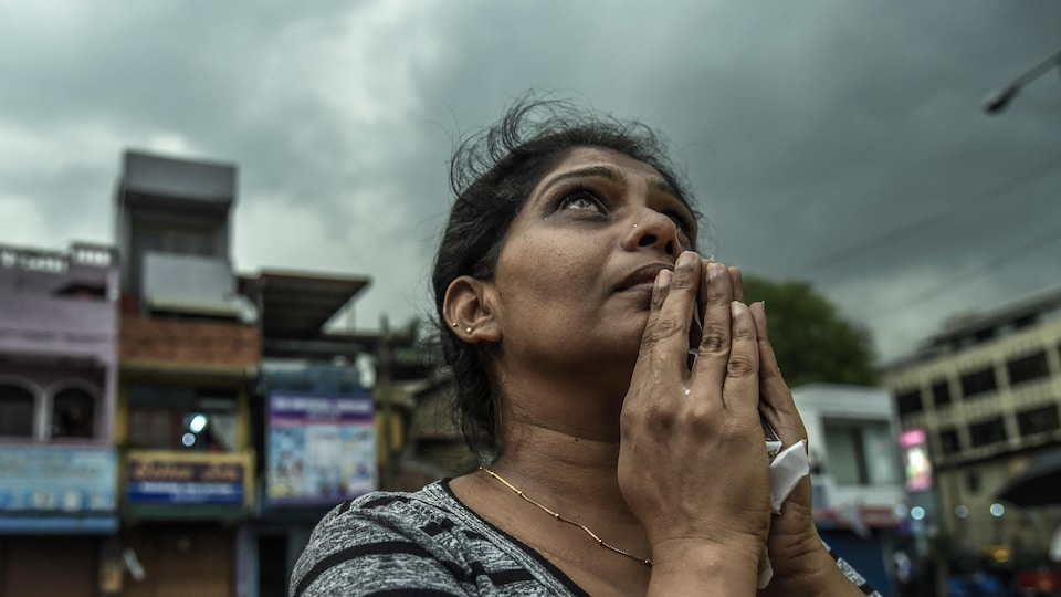 Une femme regardant vers le ciel, les mains jointes en prière.