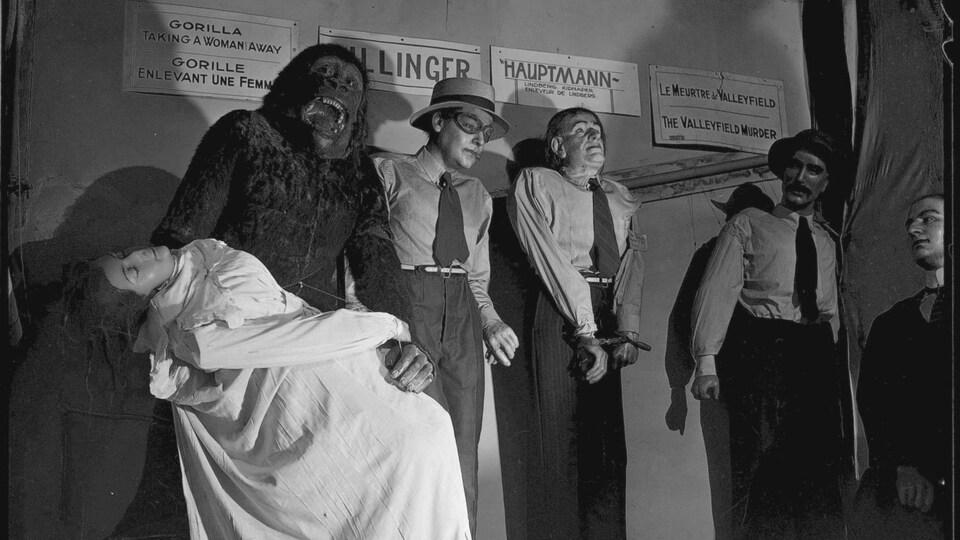 Photo en noir et blanc montrant les statues de cire d'un gorille tenant une femme évanouie et de trois hommes.