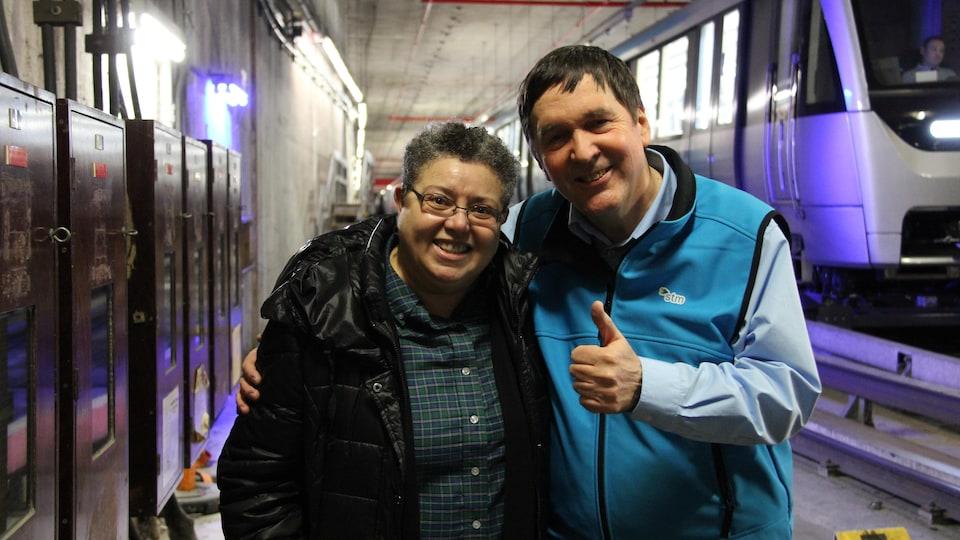 Un opérateur de métro et une femme prennent la pose pour la caméra devant un métro Azur dans un garage de la STM à Montréal.