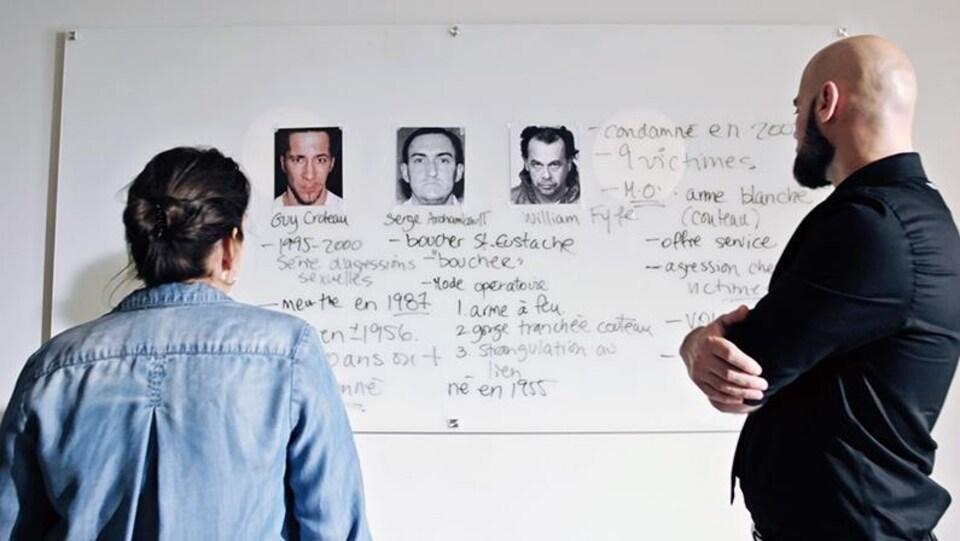 Une homme et une femme regardent en direction d'un tableau garni d'images d'hommes et d'informations.
