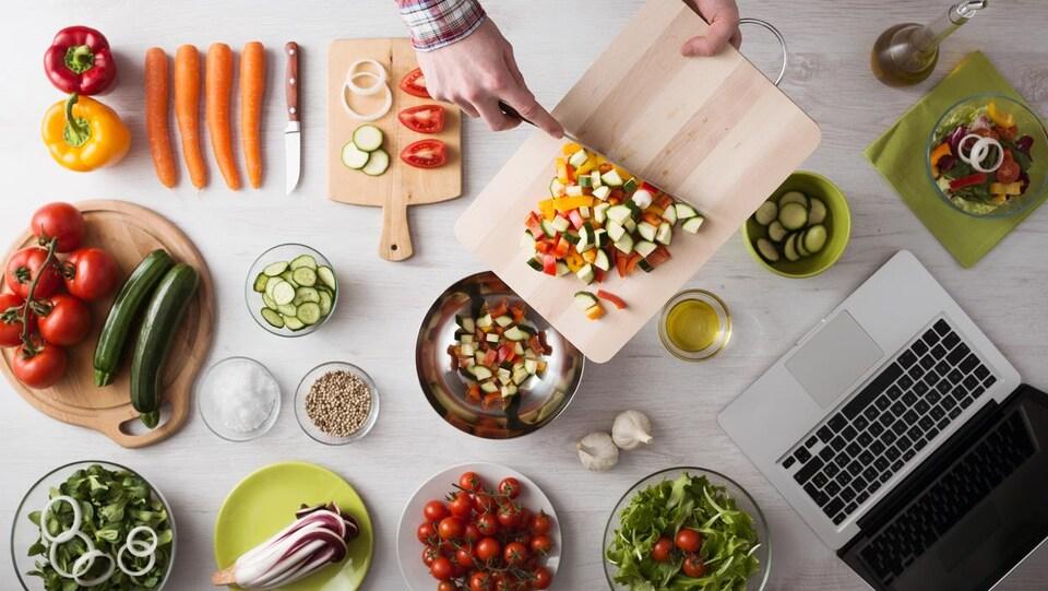 Des plats de légumes avec un ordinateur portable sur un comptoir