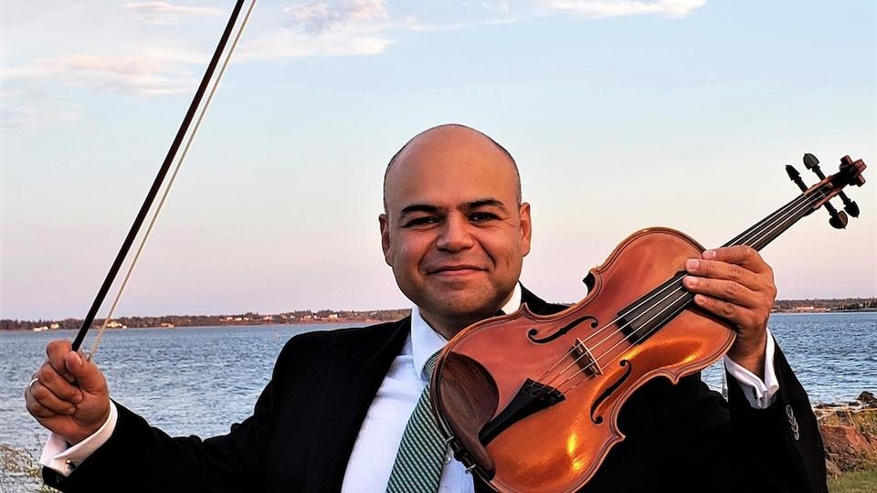 Un homme tient un violon et sourit à la caméra avec une rivière en arrière-plan.