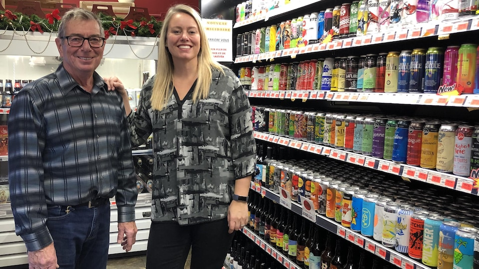 Gabriel et Nadine devant la diversité des bières offertes à leur commerce.