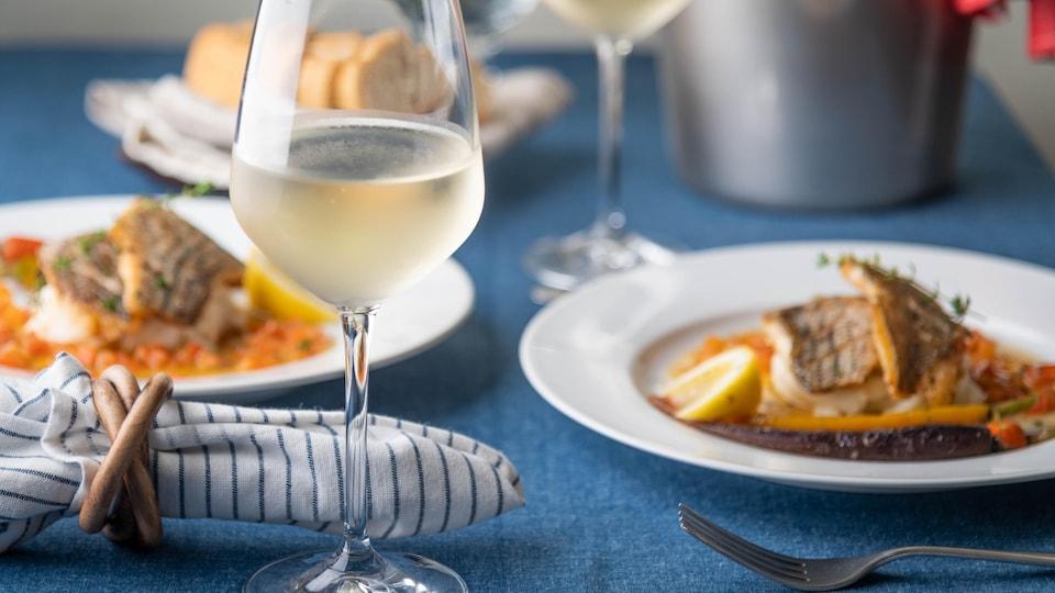 Table dressée avec deux plats de poisson poêlés et du vin blanc.
