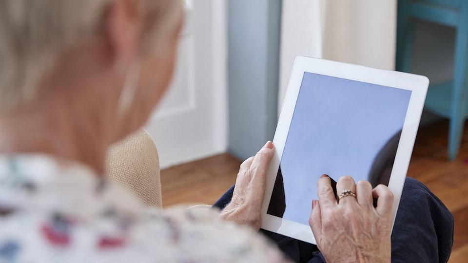 Le programme Nouveaux Horizons Une femme âgée manie une tablette électronique.