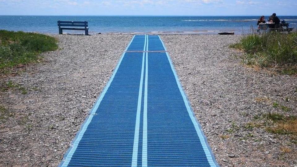 Un long tapis bleu avec des lignes blanches est déroulé sur une plage pour se rendre plus près de l'eau.