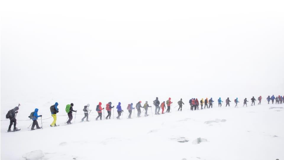 Une trentaine de personnes marchent avec des raquettes dans une tempête de neige.