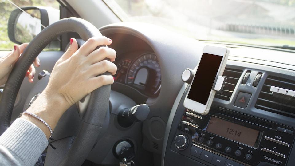 Une femme au volant, son cellulaire accroché au tableau de bord